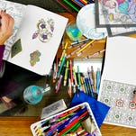 """Drinks and coloring pencils mingle on the table as Pat Sheasley of Springettsbury Township, left, and Pat Klinedinst of Springettsbury Township, right, color together during the seventh """"Coloring and Cocktails"""" at CoWork155 in York. Prime Art Supply owner Rita Whitney organizes the events, which are about once a month and which capitalize on the adult coloring book trend."""