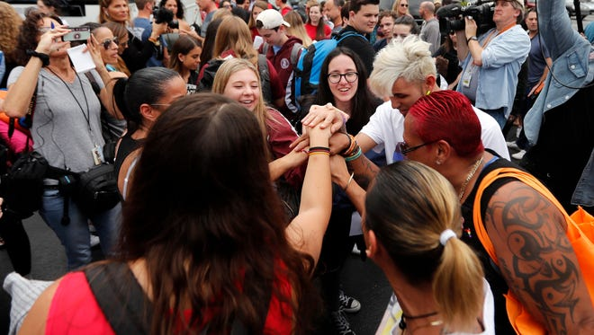 Students who survived the shooting at Stoneman Douglas High School,along with survivors of the Pulse nightclub shooting, cheer before the students board a bus in Parkland, Fla. on Feb. 20, 2018, to rally outside the state capitol and talk to legislators about gun control reform.