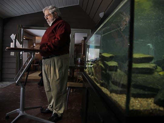 David Cay Johnston works at his stand-up desk in an enclosed porch in his Brighton home.