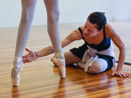 Ellen Gunn guides the feet of her student, Alyssa Cohen, into position at the Monmouth Academy of Ballet in Red Bank.