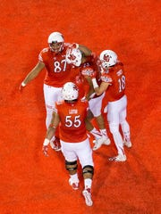 Utah Utes tight end Siale Fakailoatonga (87) and wide receiver Britain Covey (18) and offensive lineman Hiva Lutui (55) congratulate running back Devontae Booker (23) after he scored a touchdown against California.
