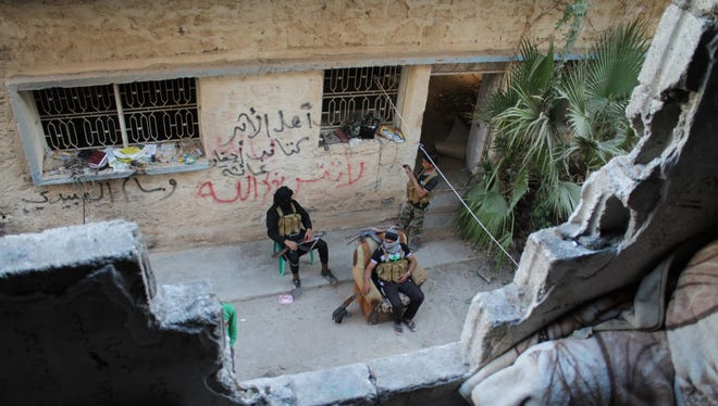 Opposition fighters sit on the front line in the Jubaila neighborhood of Syria's northeastern city of Deir Ezzor on Oct. 13, 2013.