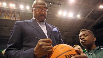 Vin Baker signs a basketball for Delijuan Perkins at a Bucks event last year. Baker is back with the Bucks as a television analyst after battling alcoholism and financial problems.