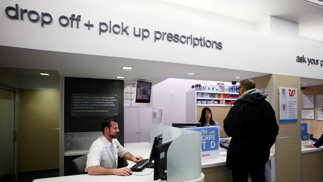 Pharmacist Dan Darlington works at his desk located next to the prescription pickup counter at the Walgreens flagship store in the Empire State Building on May 15, 2013 in New York.