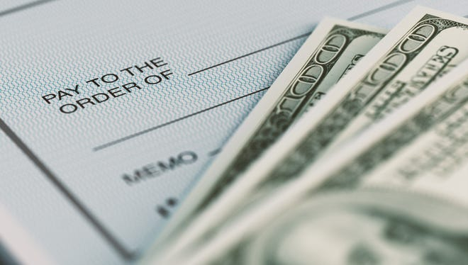 Close-up picture of a personal check and money