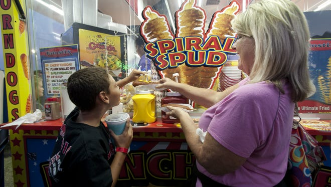 Sharon Mizner of Tulare and her grandson Jayden Mercado, 11, put mustard on a corn dog at the Tulare County Fair in Tulare on Wednesday, September 16, 2015.