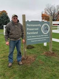 Jim Klein poses next to a sign indicating his 168-acre farm in Chester Township has been permanently preserved by the Ottawa County purchase development rights program.