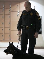 A Hamilton County sheriff's deputy prepares for a drug sweep of the Hamilton County Justice Center. At least eight K-9 units took part in a random drug sweep there Monday morning.