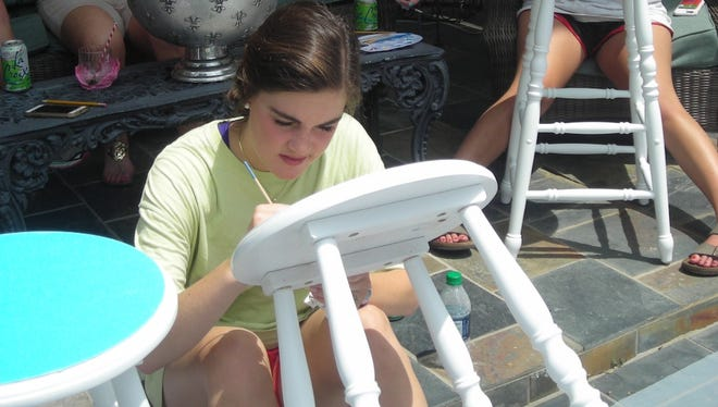 """Emily Batte is intense as she paints her stool at """"Stool Painting"""" party."""
