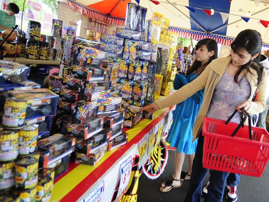 Shoppers browse fireworks at a stand in the Winco parking