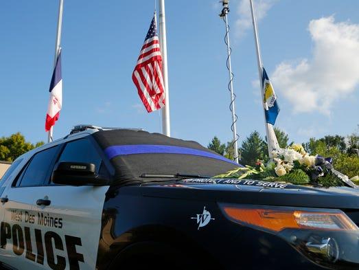 Flowers rest atop a West Des Moines Police vehicle