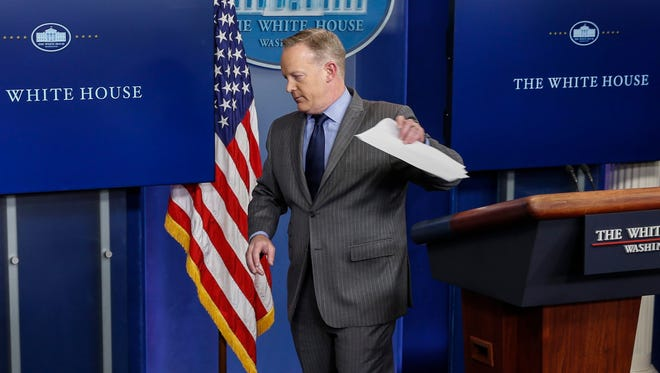 White House press secretary Sean Spicer walks from the podium without taking questions after delivering his first statement in the Brady press briefing room at the White House Saturday.