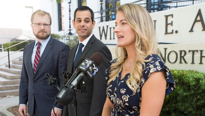 From left, attorneys Paul Sherman and Ari Bargil stand by their client, Fort Walton Beach resident Heather Kokesch Del Castillo, as she speaks to the media on Tuesday, Oct. 3. 2017, outside the Winston E. Arnow Federal Building in Pensacola. Del Castillo has filed a federal lawsuit claiming the state is violatingher First Amendment rights by requiring her to obtain a license to provide customers withdiet advice.