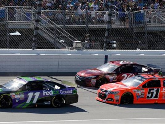 Denny Hamlin (11) drives past JJ Yeley (26) and Justin Allgaier (51) during the NASCAR Sprint Cup Series auto race at Chicagoland Speedway, Sunday, Sept. 20, 2015, in Joliet, Ill.