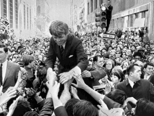 """FILE - In this April 2, 1968 file photo U.S. Sen. Robert F. Kennedy, D-NY, shakes hands with people in a crowd while campaigning for the Democratic party's presidential nomination on a street corner, in Philadelphia. Nearly 50 years after Robert F. Kennedy's assassination, a new documentary series on his life and transformation into a liberal hero is coming to Netflix. """"Bobby Kennedy for President"""" produced by RadicalMedia, Trilogy Films and LooksFilm launches Friday, April 27, 2018, on Netflix. (AP Photo/Warren Winterbottom, File)"""