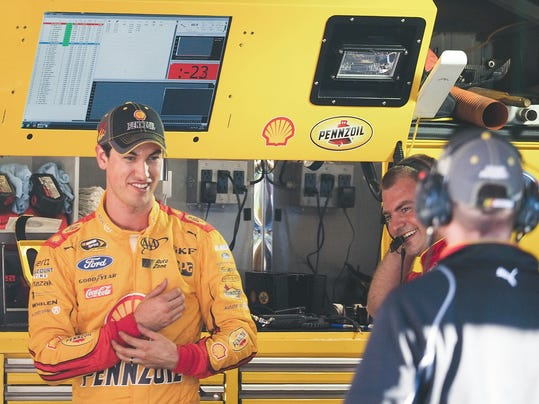 Joey Logano, left, reacts after winning the pole for Sunday's NASCAR Sprint Cup auto race at Martinsville Speedway in Martinsville, Va., Friday, Oct. 30, 2015. (AP Photo/Steve Sheppard)