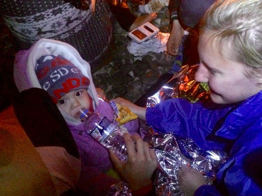 College of St. Benedict student Amy Larson smiles while providing food, water and dry clothing to a refugee baby and her family in November on the Greek island of Lesbos.