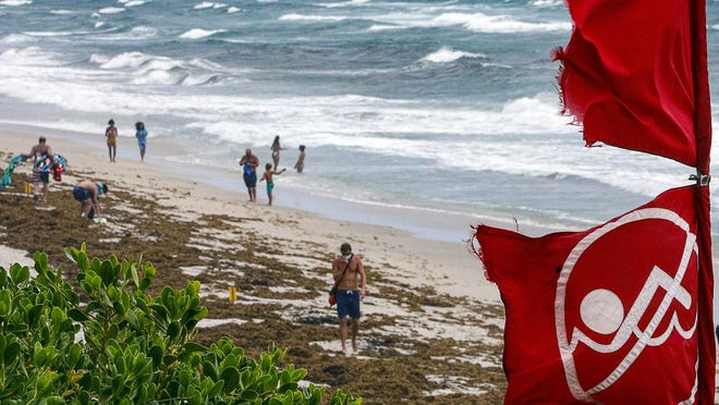 Red no swimming flags fly at Lantana Municipal Beach as Hurricane Isaias approaches the Florida coast Saturday.