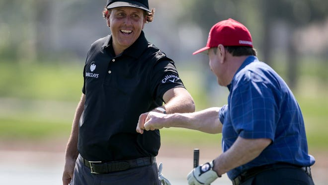 Phil Mickelson fist-bumps with John Ingram of Dallas after Ingram made a birdie on the first hole of The Honda Classic Gold Pro-Am in Palm Beach Gardens in 2014.