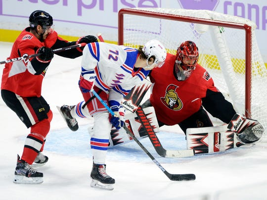 Ottawa Senators goaltender Anders Nilsson (31) makes a glove save on New York Rangers center Filip Chytil (72) as Senators' Dylan DeMelo (2) defends during the third period of an NHL hockey game Friday, Nov. 22, 2019, in Ottawa, Ontario. (Sean Kilpatrick/The Canadian Press via AP)