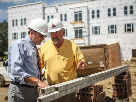 CMC President Jim Cohen, left, discusses a masonry