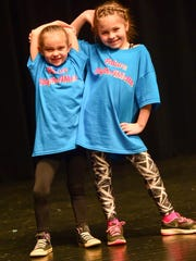 First-graders Lucy Williams (left) and Kate Wolfe strike a pose at the end of a routine on Saturday, March 5, 2016, during the RhythAMettS pom clinic at Southeast Polk High School.