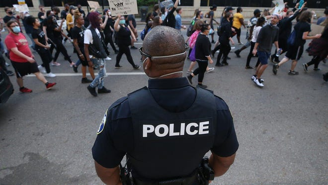 An Akron police officer watches as protesters march in the streets back to Grace Park from the Harold K. Stubbs Justice Center, Wednesday, June 3, 2020, in Akron, Ohio.