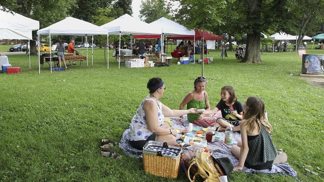 Danielle Gilbert, left, and her friend Jackie Zweifel and her daughters Reece, 11, and Lilah, 13, enjoy a picnic  during the Countryside farmers market in Akron's Highland Square neighborhood last summer.