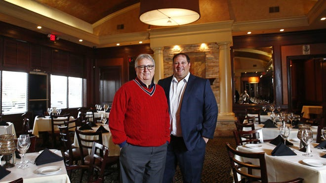 William Lalli, left, and his son, Nick Lalli, right, in Vittoria Prime Italian Steakhouse last year. William Lalli died Sunday of COVID-19.