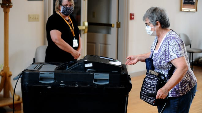 Hudson voter Pirez Rosado casts her ballot Monday at Town Hall on election day.