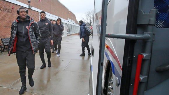 Iona men's basketball team boards a bus for the airport