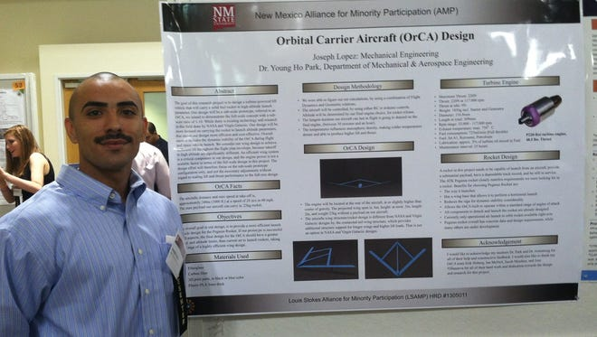 Doña Ana Community College student Joseph Lopez stands beside his presentation on Orbital Carrier Aircraft Design.