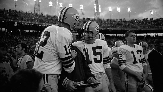Green Bay Packers quarterbacks Zeke Bratkowski (12) and Bart Starr (15) celebrate near the end of Super Bowl II against the Oakland Raiders at the Orange Bowl in Miami on Jan. 14, 1968. Quarterback Don Horn (13) is at right. The Packers won 33-14.