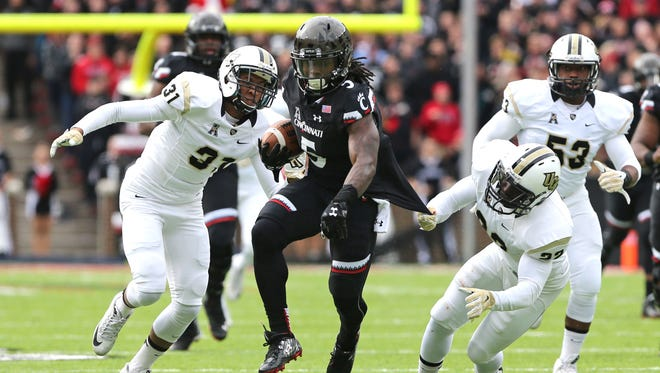 Cincinnati Bearcats running back Mike Boone breaks a tackle from UCF Knights defensive back T.J. Mutcherson in the first half at Nippert Stadium.