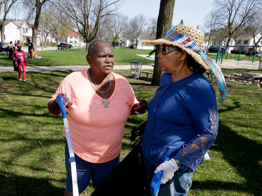 Jessie May Braggs (left) and Martha Bernice Love, residents of Garden Homes, chat as they participate in a neighborhood cleanup on May 5.