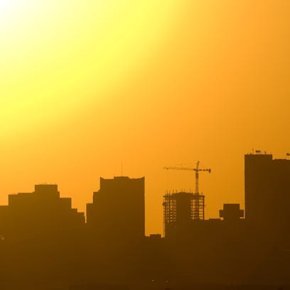 The sun sinks behind the downtown Phoenix skyline,