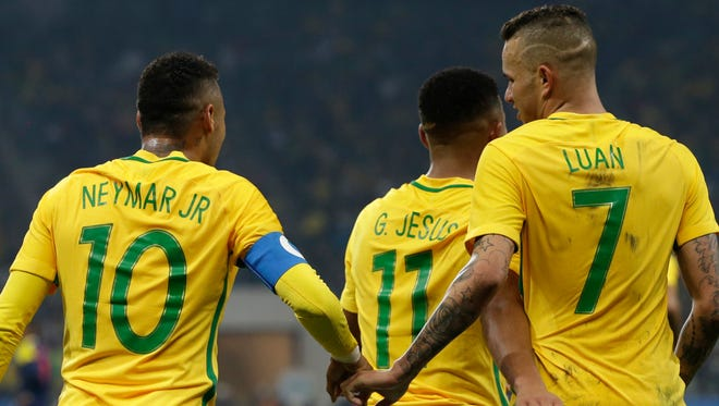 Brazil's Luan, right, celebrates with teammate Neymar after scoring against Colombia.
