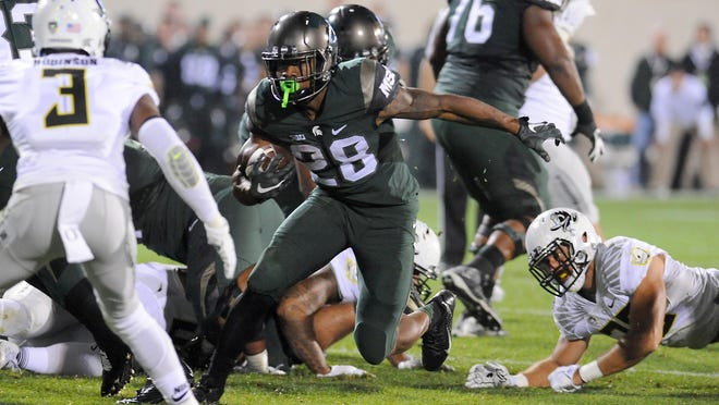MSU running back Madre London breaks through a big hole against the Oregon defense in the first half Saturday at Spartan Stadium.