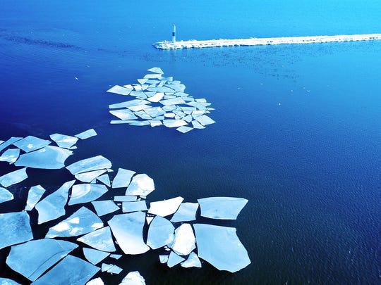 Sheets of ice float on Lake Michigan just inside the