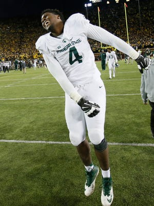 Michigan State's Malik McDowell leaps for joy as he runs across the field after the last-second 27-23 win over Michigan.
