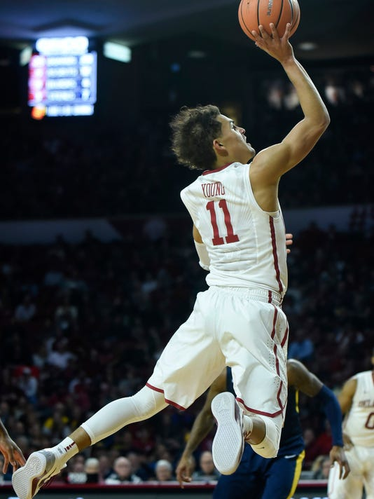 FILE - In this Feb. 5, 2018, file photo, Oklahoma's Trae Young goes up for a shot in the second half of an NCAA college basketball game against West Virginia in Norman, Okla. Oklahoma star freshman Trae Young is leaving for the NBA after a standout season. The 6-foot-2 guard averaged 27.4 points and 8.7 assists this season, and many projections have him going early in the first round. He posted the reasons for his decision on ESPN early Tuesday, March 20, 2018, saying he was ready to put in the work needed to play in the NBA. (AP Photo/Kyle Phillips, File)