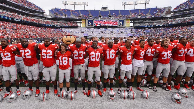 Members of the Ohio State football team sign following their win Saturday against Navy at M&T Bank Stadium.