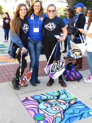 First place winners Erin Miller and Halie Dawkins in front of their artwork with their art teacher Kristin Manos