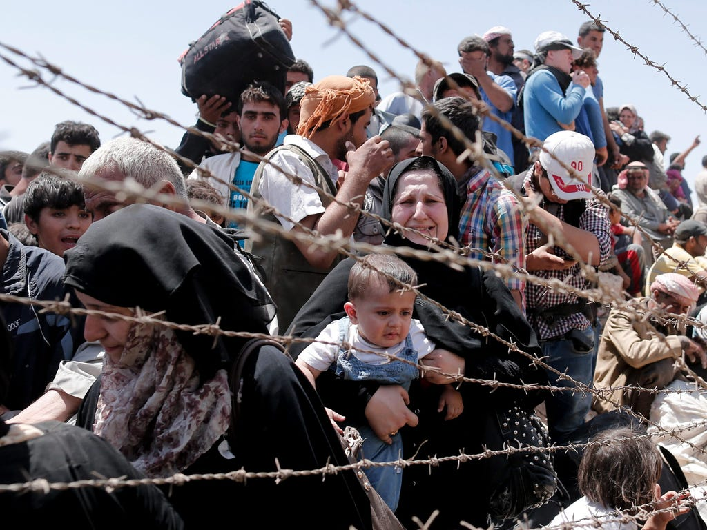A picture taken from the Turkish side of the border between Turkey and Syria shows Syrian refugees waiting on the Syrian side of the border crossing near Akcakale, Sanliurfa province, south-eastern Turkey.