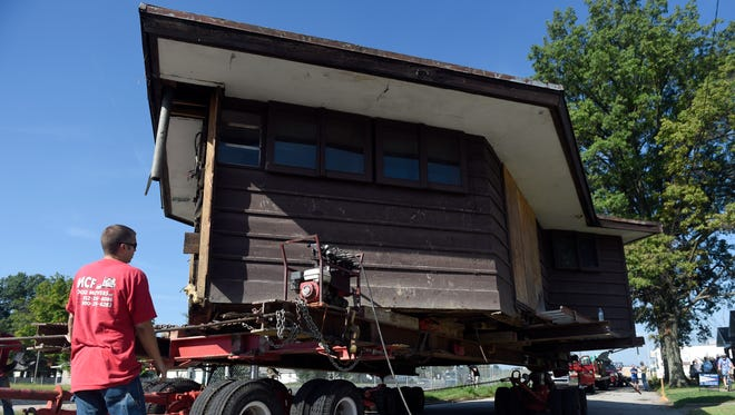 Alex Deffendoll of MCF House Movers watches as the company makes adjustments while transporting the Peters-Margedant house along E. Division Street in Evansville Thursday.  The house was transported to its new location on the University of Evansville campus.