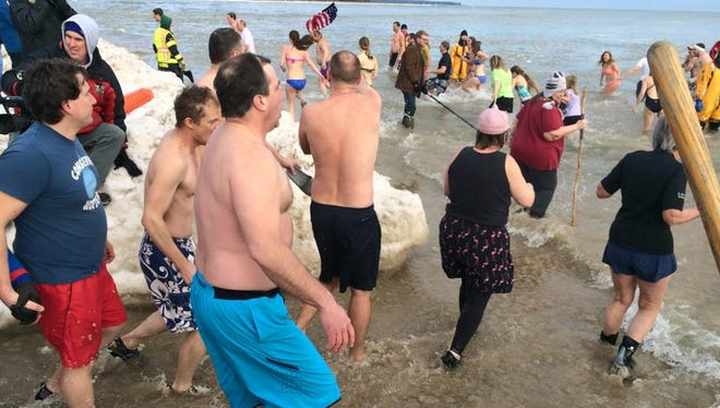 Swimmers head into Lake Michigan in Jacksonport on Thursday as part of the annual polar bear swim.