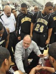 Arlington basketball coach Larry Nicks talks to players