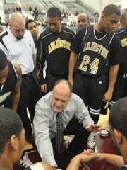 Arlington basketball coach Larry Nicks talks to players