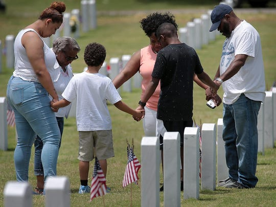 The family of Henry Bates prays over his grave during a visit after the Memorial Day Ceremony at the West Tennessee State Veterans Cemetery Monday afternoon.