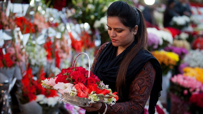 A girl buys flowers to celebrate Valentine's Day, in Islamabad, Pakistan, on Feb. 13, 2017.